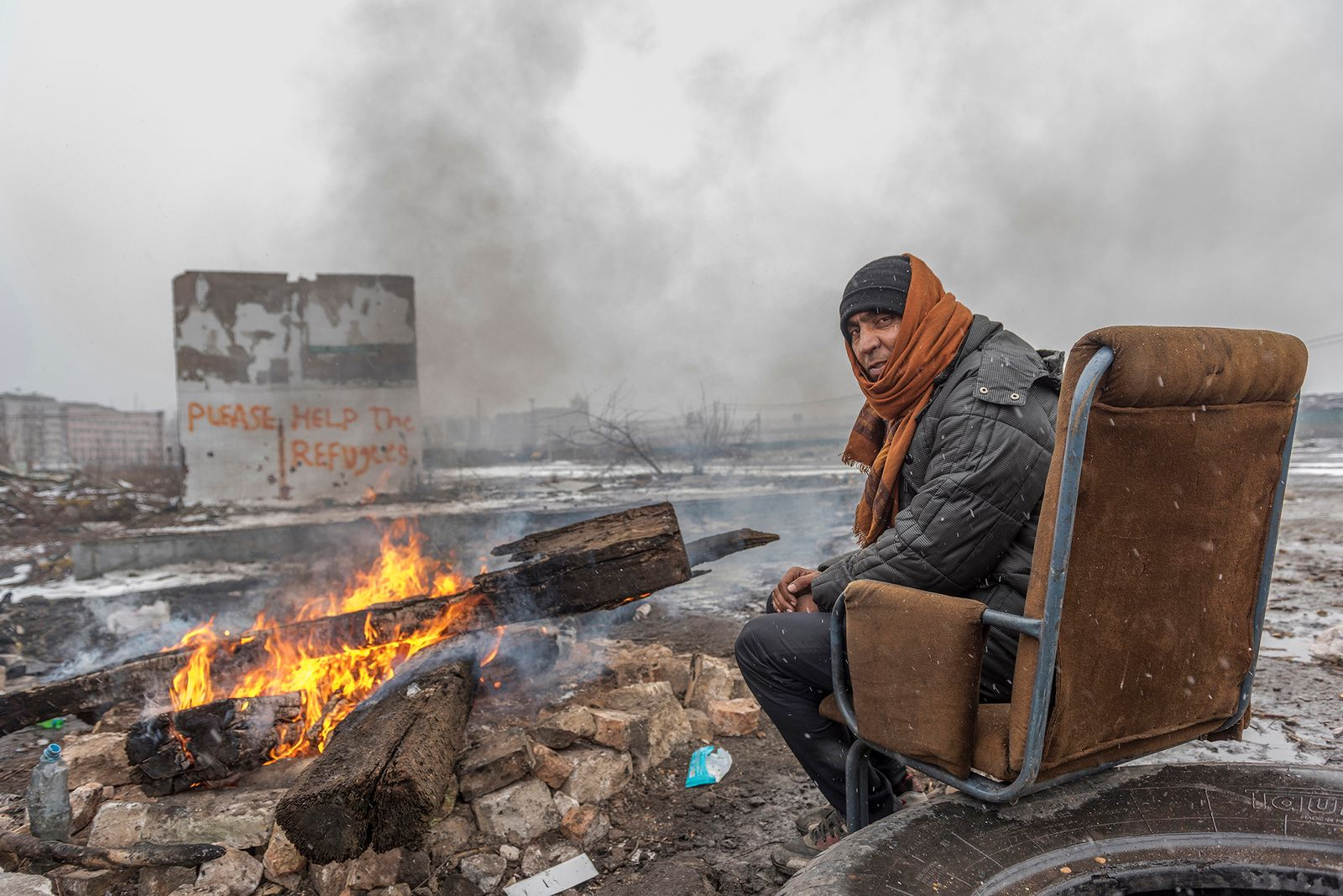 Barracks of Belgrade, a refugee man tries to keep warm